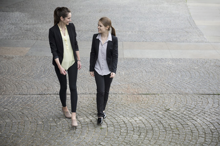 Elevated view of two caucasian business women talking outside modern office buidling. Stock Photo