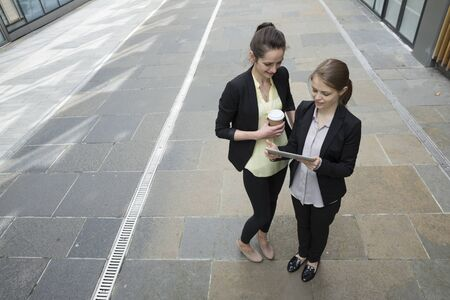Elevated view of two Caucasian Business women using digital tablet computer.