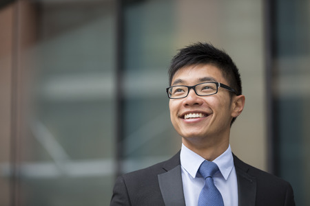 asian adult: Portrait of a Chinese businessman outside modern office building, looking away. Stock Photo
