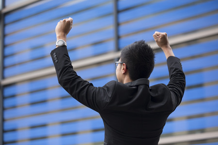 asia people: Chinese businessman outside office building with his arms raised celebrating his success. Concept about a freedom and achievement.