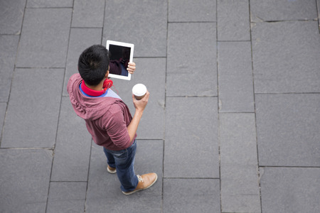 High angle view of a Chinese man standing on city street using a tablet device. Banque d'images
