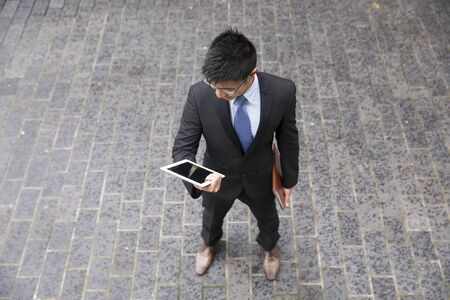 high angle: High angle view of a Chinese man standing on city street using a tablet device. Stock Photo