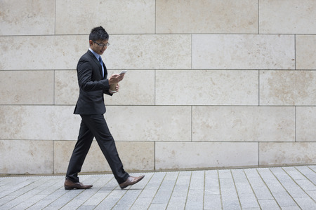 sideview: Portrait of a confident asian businessman walking in the city. Stock Photo