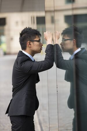 banging: Angry and desperate Chinese businessman standing outside office building.