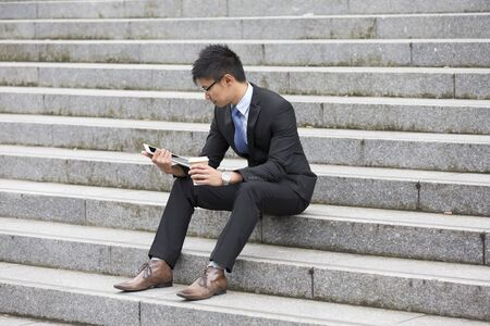 using tablet: High angle view of a Chinese man sitting on steps using a tablet device outdoors.