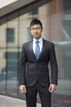 young man portrait: Portrait of a Chinese businessman outside modern office building. Asian businessman smiling & looking at the camera with blurred office buildings as a background. Stock Photo