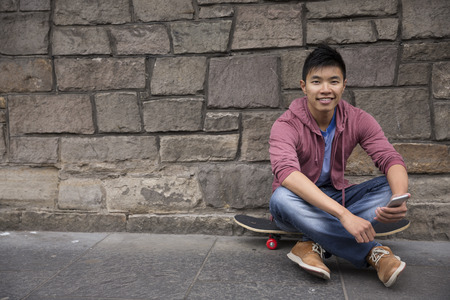 Portrait of a Asian man using his Smart Phone and holding his skateboard. Standing outdoors in city street. Stock Photo