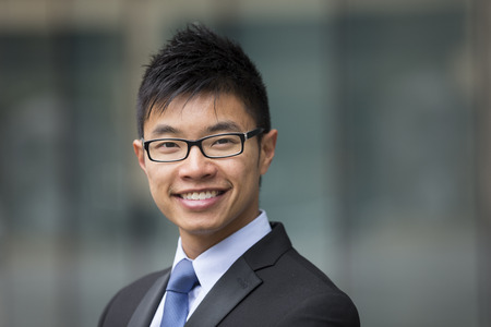 asian lifestyle: Portrait of a Chinese businessman outside modern office building. Asian businessman smiling & looking at the camera with blurred office buildings as a background. Stock Photo