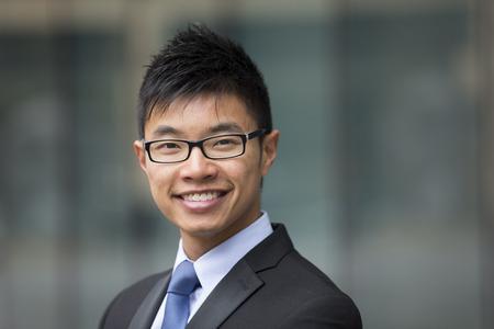 ejecutivos: Retrato de un hombre de negocios chino fuera moderno edificio de oficinas. Hombre de negocios asiático sonriendo y mirando a la cámara con edificios de oficinas borrosa como fondo.