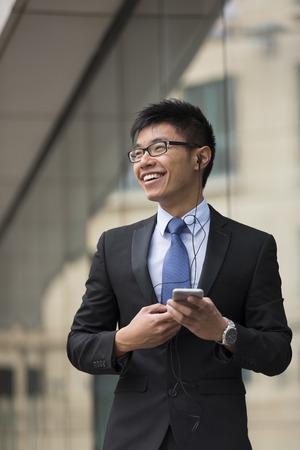 handsfree: Chinese business Man using his Smart phone with handsfree kit. Stock Photo