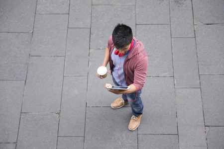 High angle view of a Chinese man standing on city street using a tablet device.