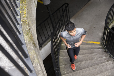 elevated view: Athlete Chinese man running outdoors in urban city. Asian running man, listening to music on smart phone while running up stairs. Sporty Male fitness concept.