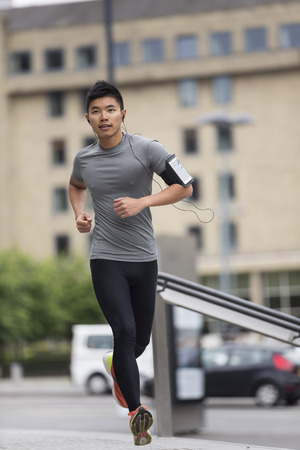 Athlete Chinese man running outdoors in urban city. Asian running man, listening to music on smart phone while running. Sporty Male fitness concept. Stock Photo