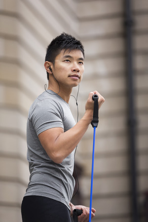 elastic band: Portrait of an athletic Chinese man using stretch bands outdoors in urban setting.