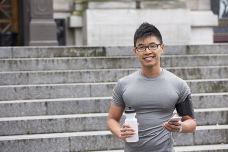 and athlete: Retrato de hombre chino deportivo descansando despu�s del rodaje urbano a trav�s de calles de la ciudad. Asi�tico corredor masculino que toma la rotura de pie relajante.