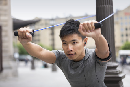 Portrait of an athletic Chinese man using stretch bands outdoors in urban setting.