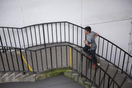 hombre deportista: Atleta chino correr al aire libre en la ciudad urbana. Hombre corriendo asiática, escuchar música en el teléfono inteligente durante la ejecución de las escaleras. Sporty concepto de fitness masculino.
