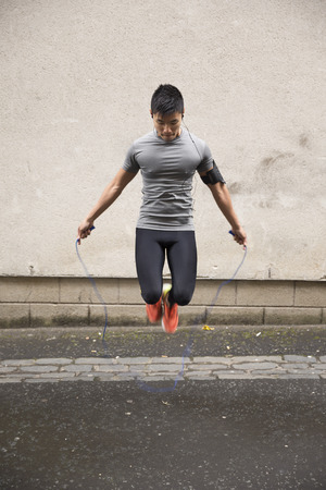 rope background: Portrait of athletic Chinese man using a skipping rope in a city street.