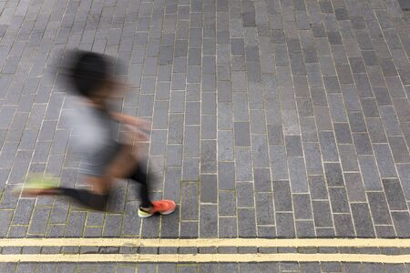 runner: Motion blurred view of a man running. High angle view of a Asian man running on street. Male fitness concept.
