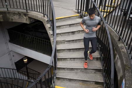 running man: Athlete Chinese man running outdoors in urban city. Asian running man, listening to music on smart phone while running up stairs. Sporty Male fitness concept.