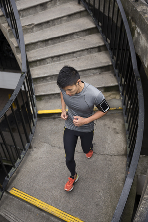 hombres corriendo: Atleta chino correr al aire libre en la ciudad urbana. Hombre corriendo asiática, escuchar música en el teléfono inteligente durante la ejecución de las escaleras. Sporty concepto de fitness masculino.