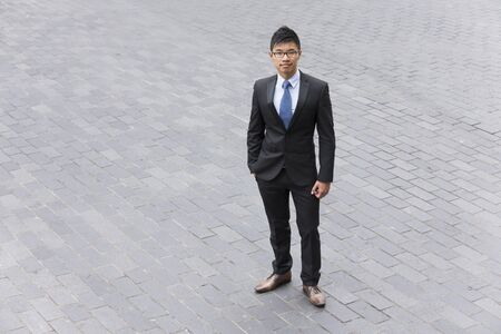 chinese businessman: High angle view of a Chinese businessman standing in the street. Stock Photo
