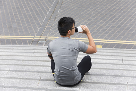 man drinking water: Portrait of an athletic Chinese man drinking during outdoors workout. Asian male runner taking break and drinking water. Stock Photo