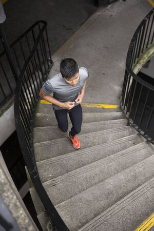 Athlete Chinese man running outdoors in urban city. Asian running man, listening to music on smart phone while running up stairs. Sporty Male fitness concept.