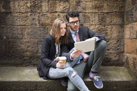 couple outdoor: Stylish Caucasian couple using a digital tablet outdoors in the city.