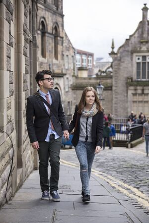 romantic man: Romantic happy couple walking down the street in europe. Young man and woman walking together. Stock Photo