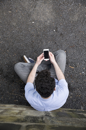 unusual angle: High angle view of a young man using a Smart phone outdoors.