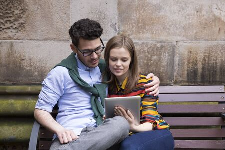 using tablet: Stylish Caucasian couple using a digital tablet outdoors in the city.