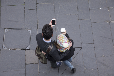 above: High angle view of a couple walking down the street using a Smart Phone. Young man and woman walking together. Stock Photo