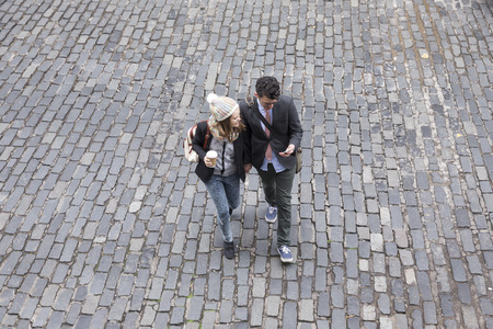 High angle view of a couple walking down the street using a Smart Phone. Young man and woman walking together. 스톡 콘텐츠