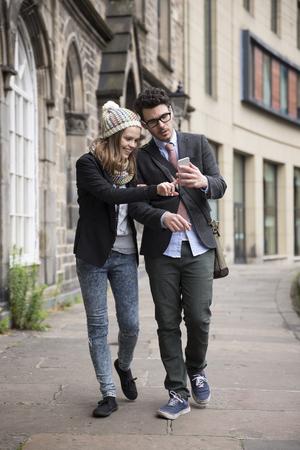 persona caminando: Cauc�sico pareja feliz caminando por la calle usando un tel�fono inteligente. Hombre joven y mujer caminando juntos.