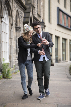 street love: Happy Caucasian couple walking down the street using a Smart Phone. Young man and woman walking together.