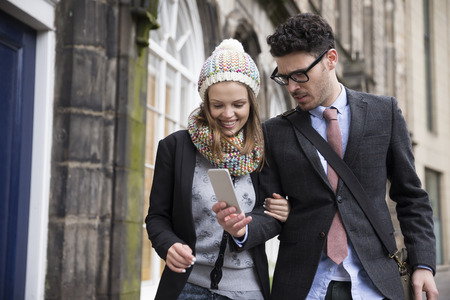 Happy Caucasian couple walking down the street using a Smart Phone. Young man and woman walking together.