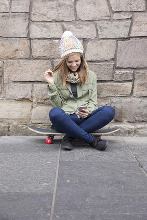 using phone: Portrait of a Young woman holding skateboard and using her Smart Phone. Stock Photo