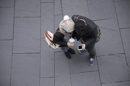 unusual angle: High angle view of a couple walking down the street using a Smart Phone. Young man and woman walking together. Stock Photo