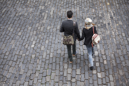 walking down: High angle view of a couple walking down the street using a Smart Phone. Young man and woman walking together. Stock Photo
