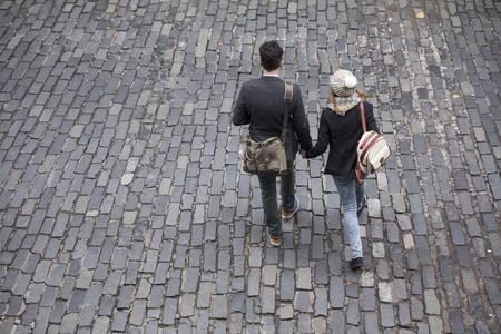 persona caminando: Vista de ángulo alto de una pareja caminando por la calle usando un teléfono inteligente. Hombre joven y mujer caminando juntos. Foto de archivo
