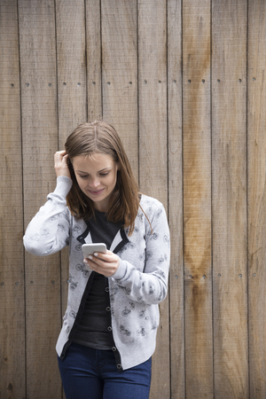 cell phone booth: Young casual woman using her smartphone. Caucasian femake model using a phone. Stock Photo