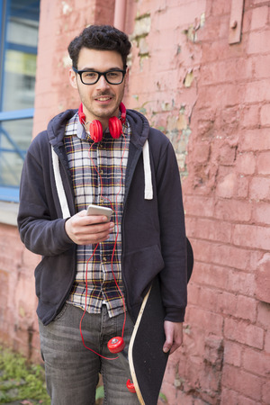 cool guy: Portrait of a trendy urban man using his Smart Phone and holding a skateboard.