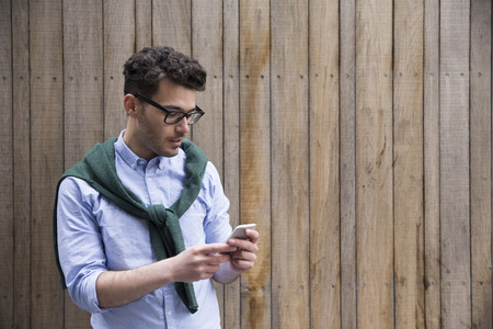Portrait of young man using a smart phone outdoors.