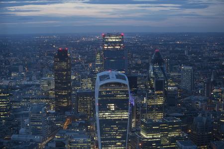 aerial: Vista aérea de la ciudad de Londres en la oscuridad. Con el distrito financiero en el primer plano.
