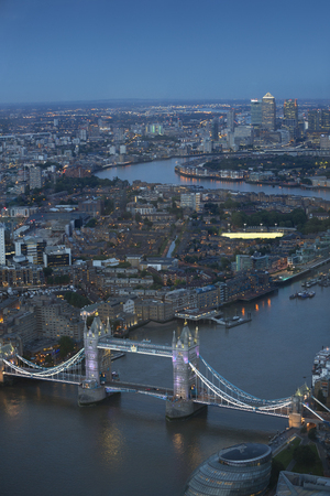 forground: Aerial view of London at night. With the River Thames and Tower Bridge in the forground and Canary Wharf in the distance. Stock Photo