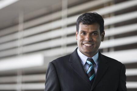 worker man: Portrait of an Indian businessman outside modern office building.