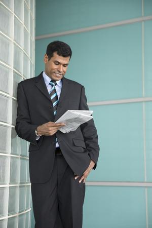 periodicos: hombre de negocios indio feliz mirando hacia abajo y la lectura de un periódico.