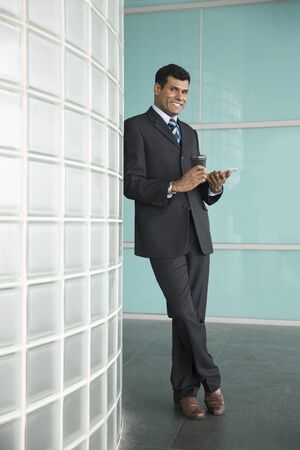 well read: Happy Indian business man holding a digital Tablet device.