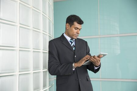 man looking down: Happy Indian business man using his digital Tablet device. Stock Photo